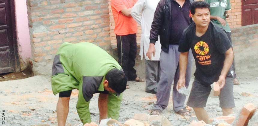 CARE staff member helps move rubble