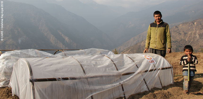 Uttam at his vegetable farm with plastic sheeting greenhouses