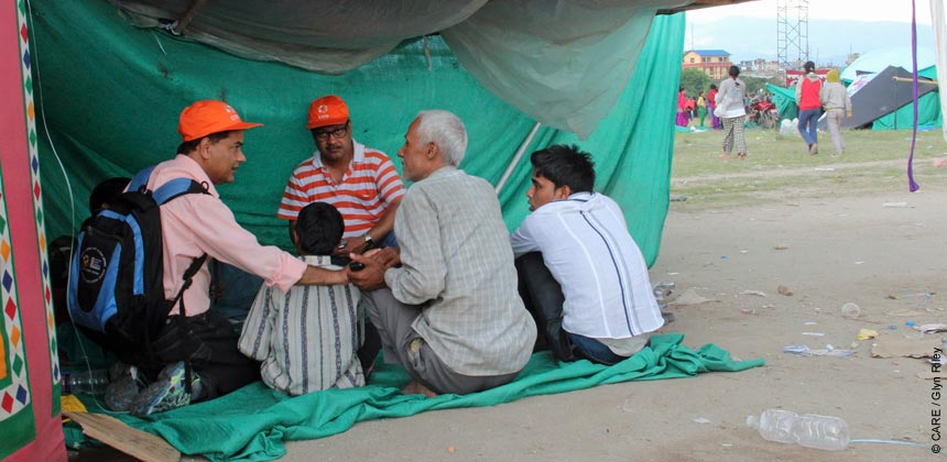 CARE's Santosh Sharma talking to a family at the Kathmandu tent camp