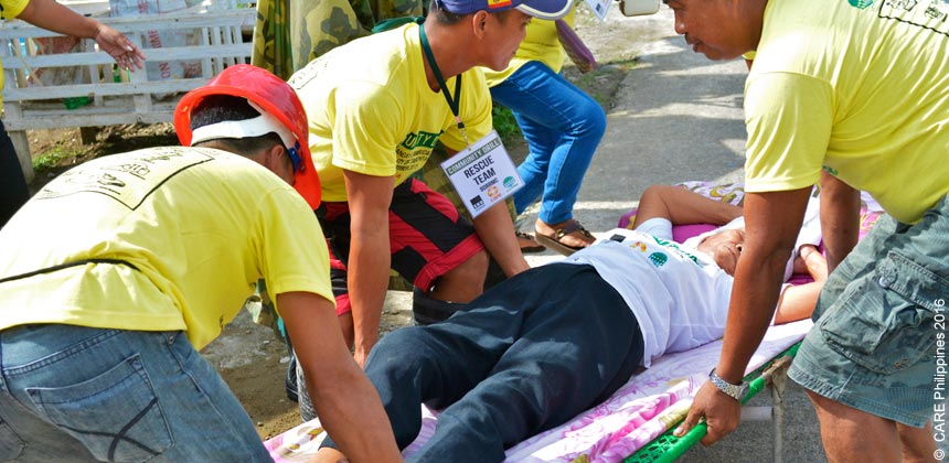 People carrying a woman on a stretcher during a community drill