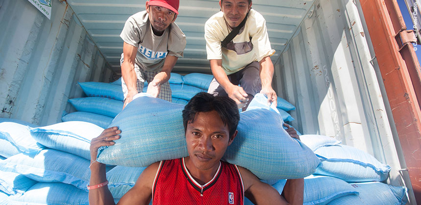 Workers unload sacks of grain for distribution