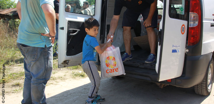 A young Iraqi boy receives a CARE package including diapers, wipers, baby food and disinfectant for his two younger sisters