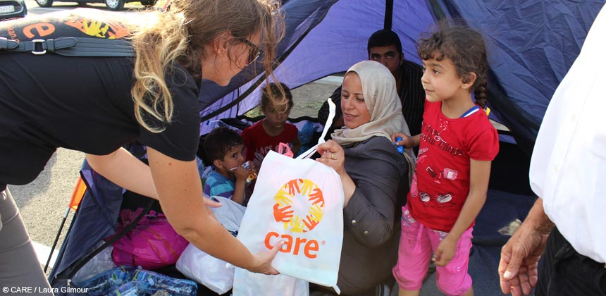 CARE staff member provides family in tent with emergency supplies
