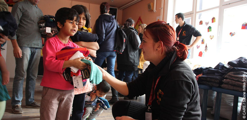 A volunteer giving clothes to a child
