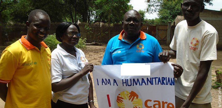 CARE South Sudan staff holding a banner
