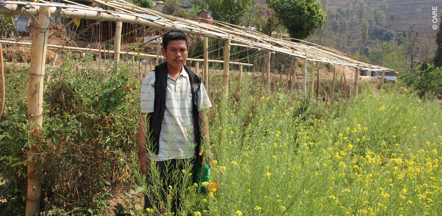 Som Bahadur tamang stands in front of his tunnel farm supported by CARE