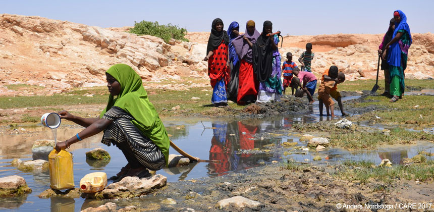 Women at a drying-out water source in Somalia