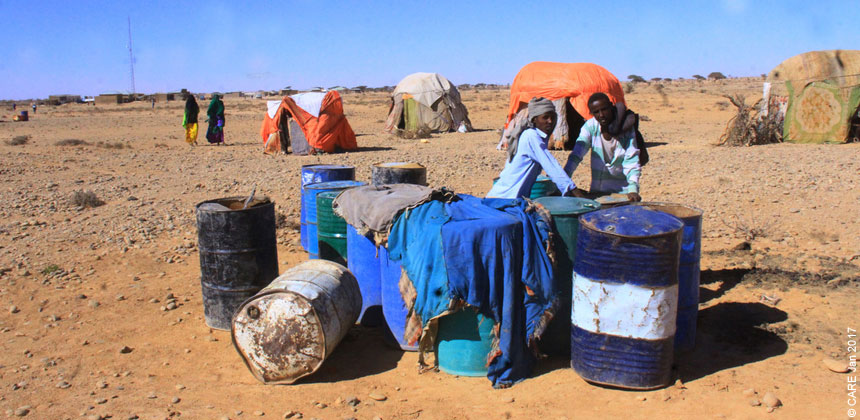 People and water drums in scrubland in Somalia