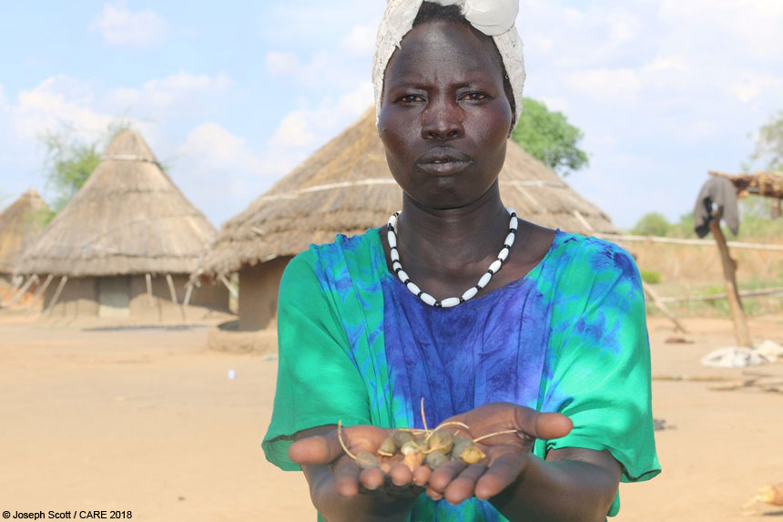 Mary Amal holding wild fruits in South Sudan