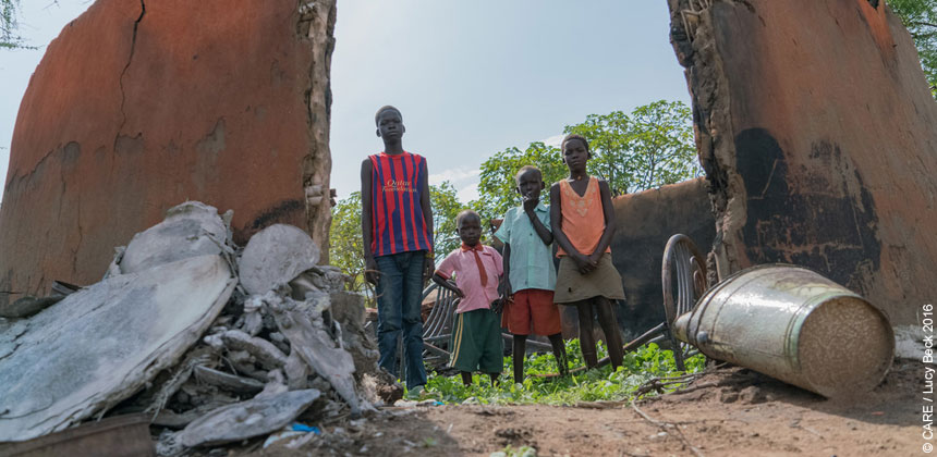 Children stand in burnt-out shell of home