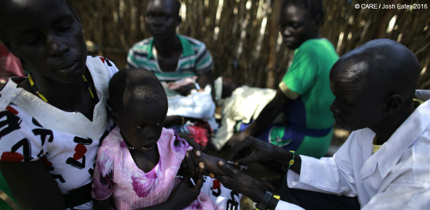 Medical staff give an injection to a young girl