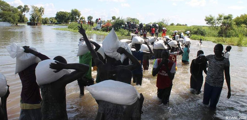 People wading across flooded fields in South Sudan