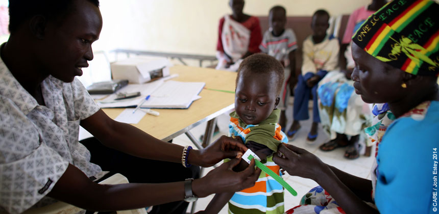 Medical staff test a child for signs of malnutrition