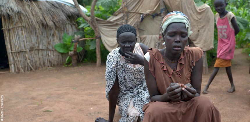A woman sitting in front of huts in South Sudan