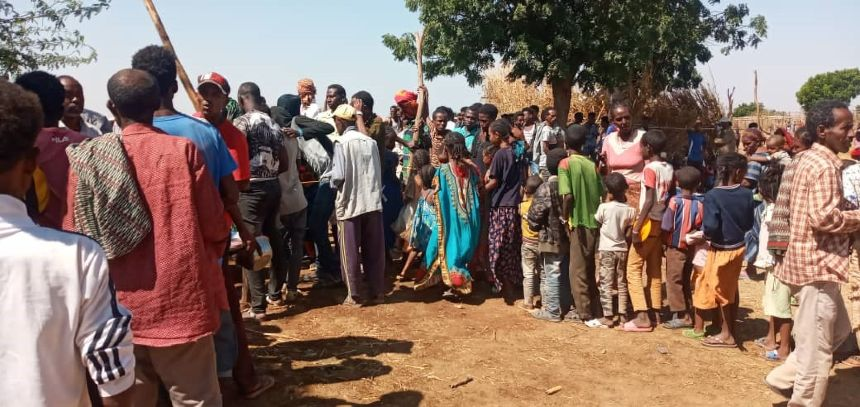 People waiting in line for aid at refugee camp in Sudan