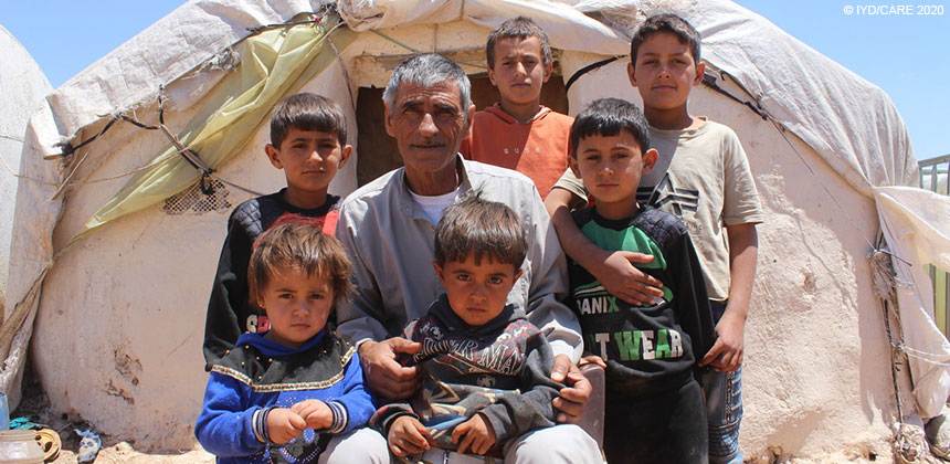Abdullah and family outside tent at displaced persons camp in Syria