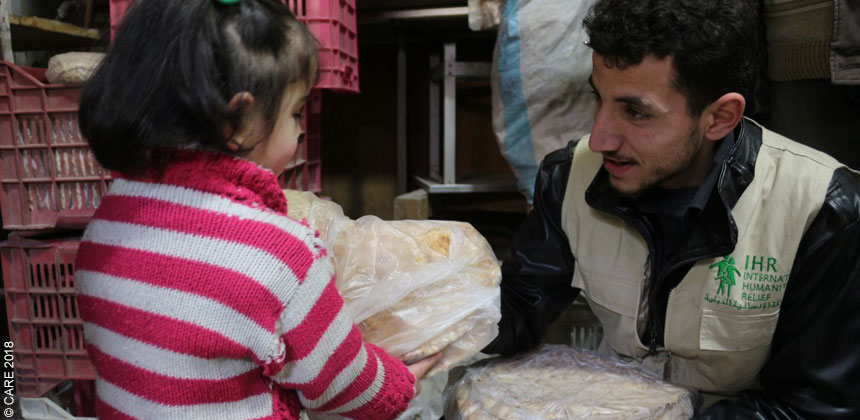 An aid worker gives bread to a girl in Syria