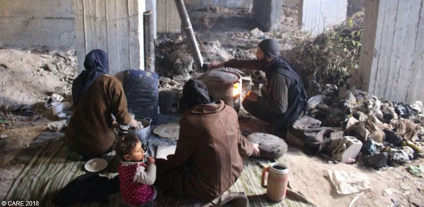 Family cooking in damaged building in Eastern Ghouta, Syria