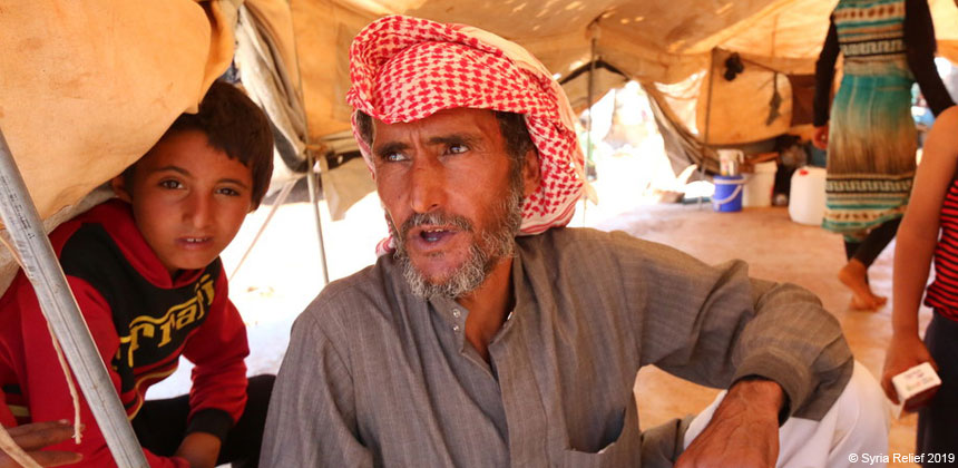 A man and child in tent camp in Idlib, Syria