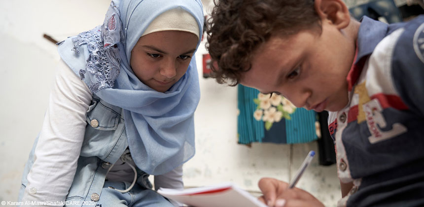 Maram helping her family member with his schoolwork, in Syria