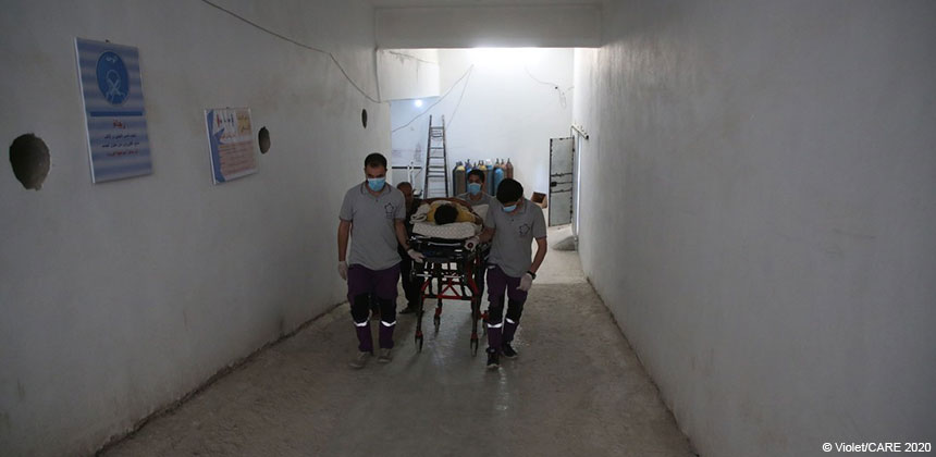 A patient being moved on a trolley bed in a hospital corridor in Syria