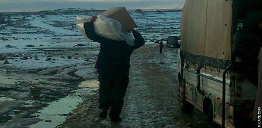 A man carrying a box of supplies in a wintry landscape in Syria