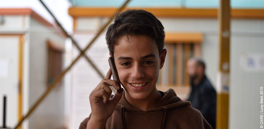 A Syrian refugee boy holding a mobile phone