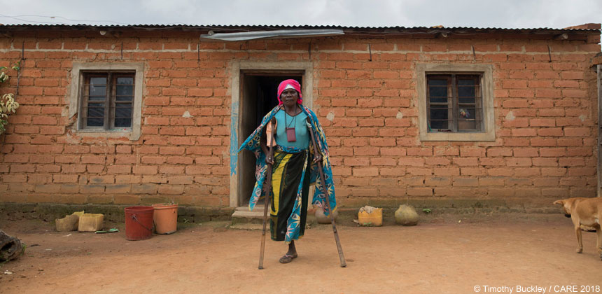 Josafina, a disabled woman in Tanzania, outside her home