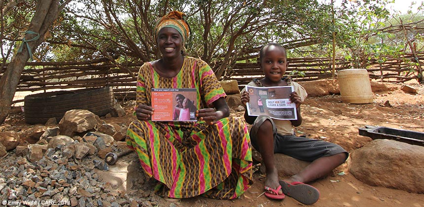 Rehema and her daughter in Tanzania, holding CARE posters