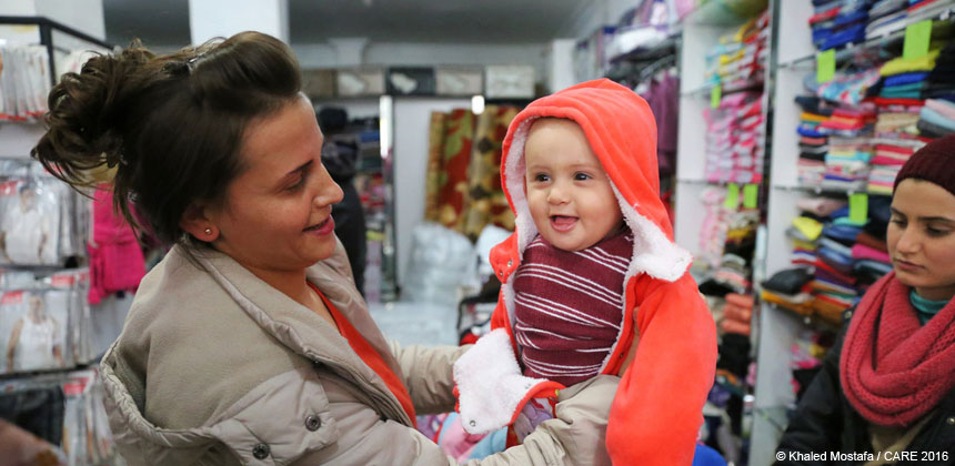 Mother holding smiling baby in shop in Turkey