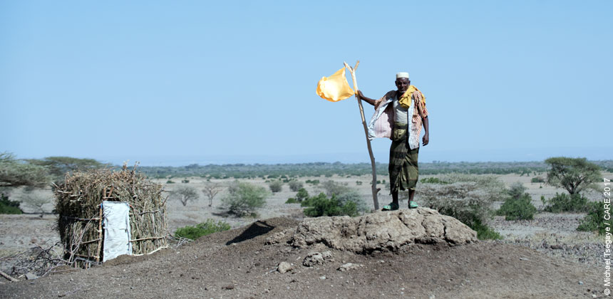 A man holding a flag next to a latrine