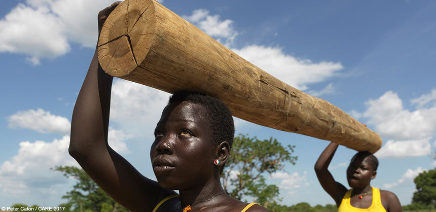 Two young women carrying wood