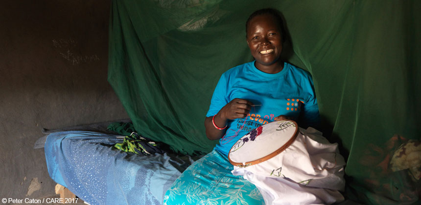 Joyce with her embroidery inside her home in the refugee settlement