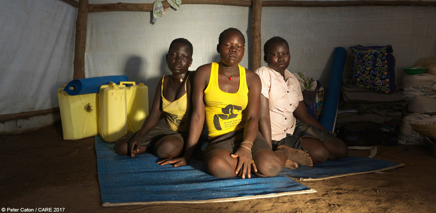 Three young women inside a temporary shelter