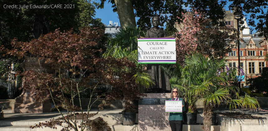 """Helen Pankhurst holds a sign reading """"Courage calls for climate action everywhere"""" in front of the Millicent Fawcett statue in Parliament Square. The statue is surrounded by plants and flowers."""
