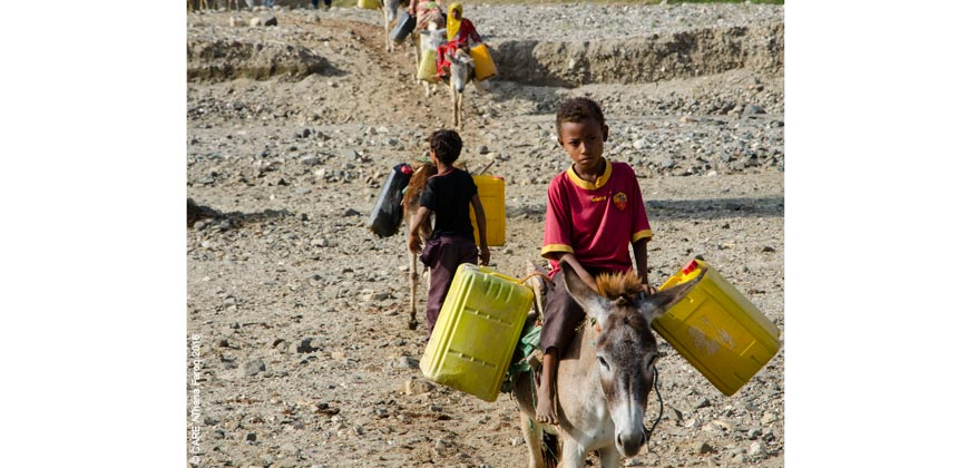 Boys on donkeys carrying water