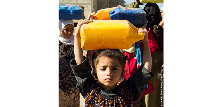A young girl carrying a jerry can