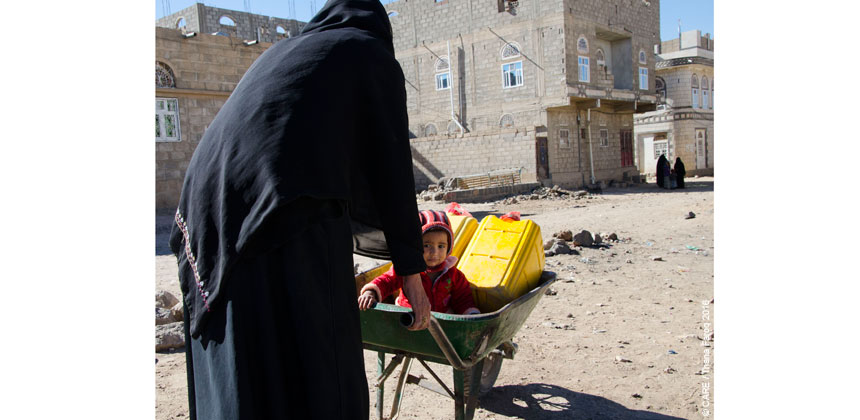 A woman pushes a child and a water can in a wheelbarrow