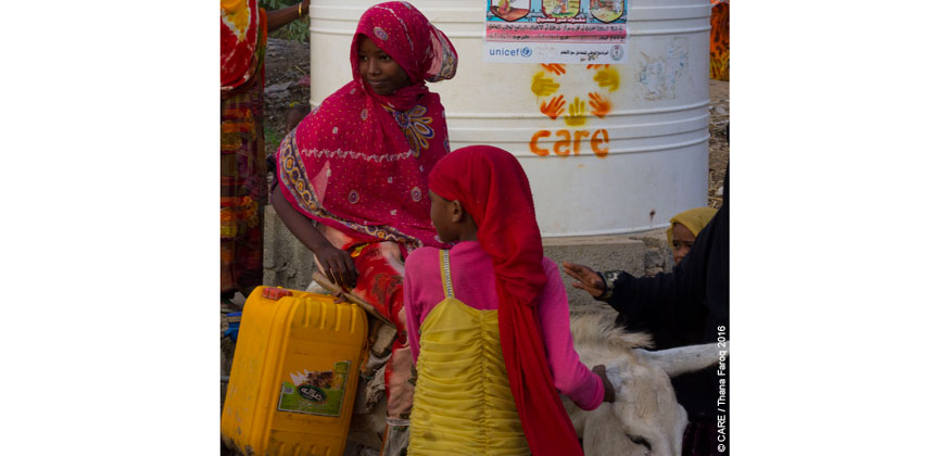 Girls collecting water from a CARE water tank