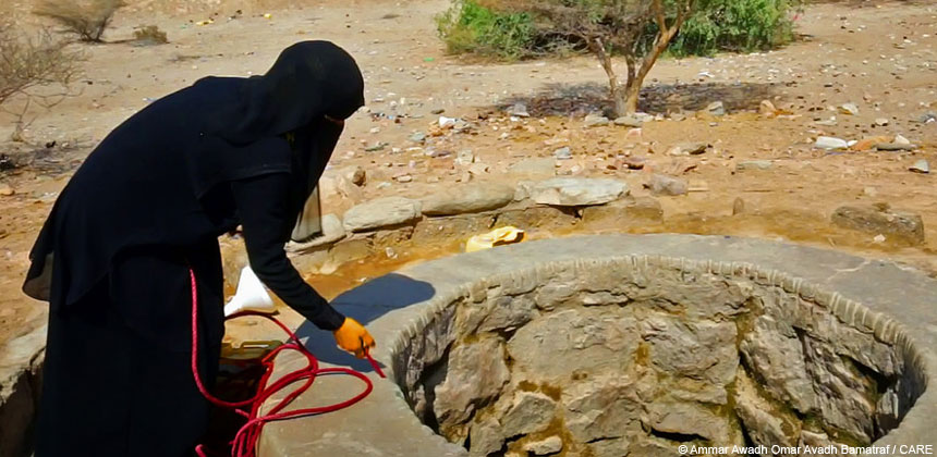A woman collecting water from a well in Yemen