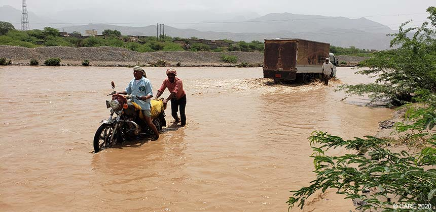 Motorbike and lorry on flooded road, Yemen