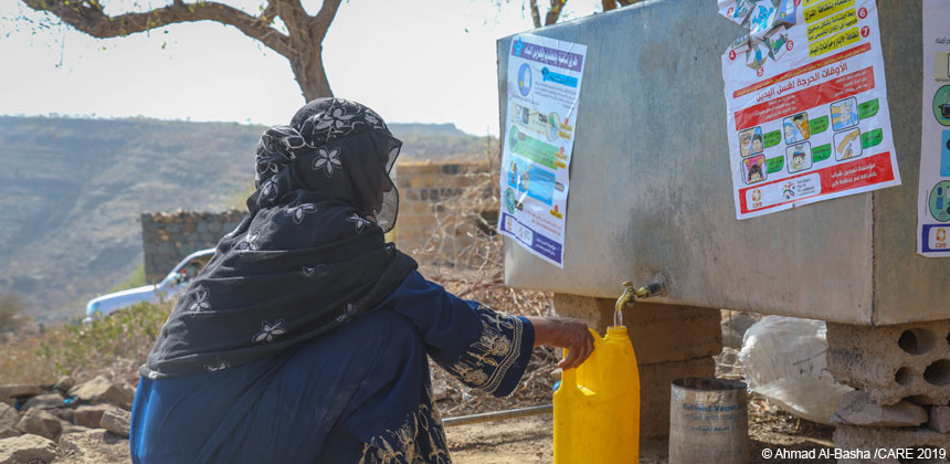 A woman collecting water from a water tank in Yemen
