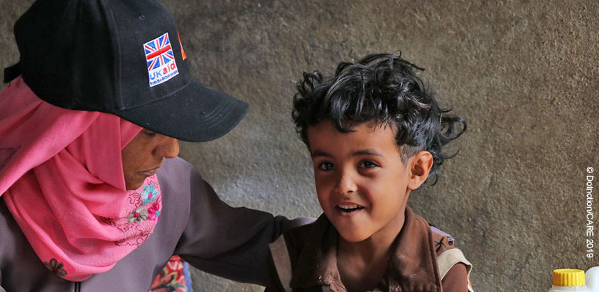 Woman in UKaid cap with young boy in Yemen