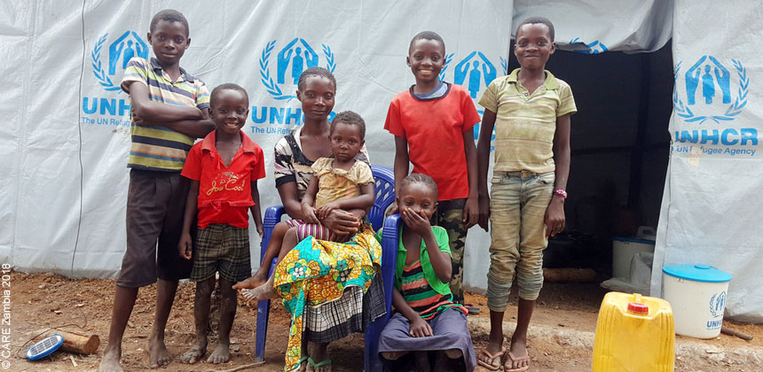 A family in front of their shelter at a refugee camp in Zambia