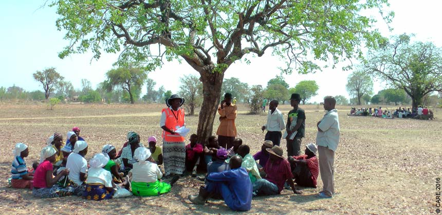 A group of people meeting under a tree