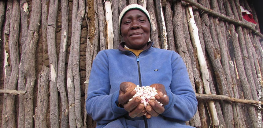 A woman in Zimbabwe holding food grains