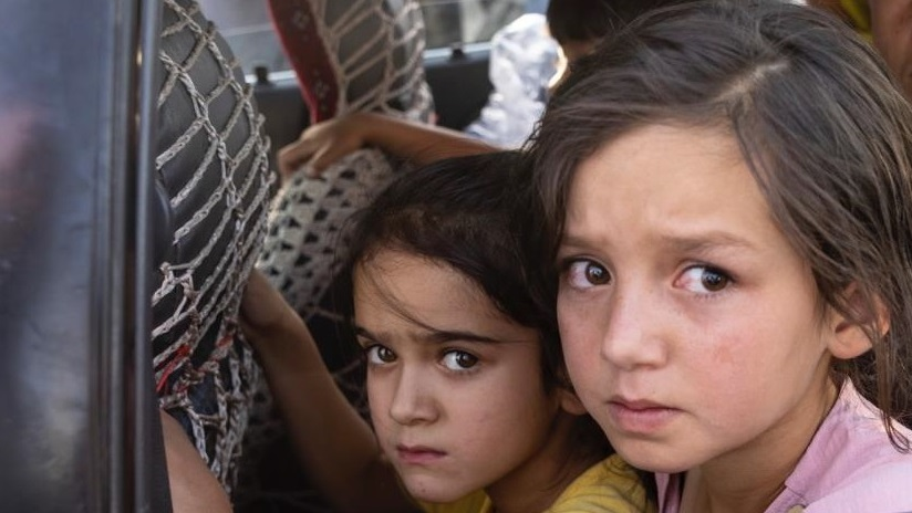 Children await transport following the esacaltion of conflict in Afghanistan.
