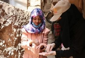 Malak recieves training on how to hygienically wash her hands from CARE community worker, Samah
