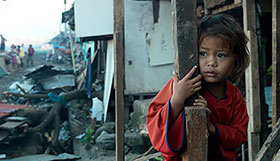 A girl looks out at the devastation of her town after Typhoon Haiyan