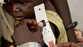 A South Sudanes baby is assessed by a health worker